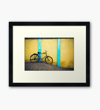 Bicycle against wall Framed Print