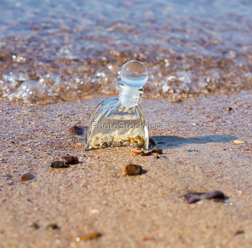 A bottle with seashells embedded in the sand on the beach  by PhotoStock-Isra