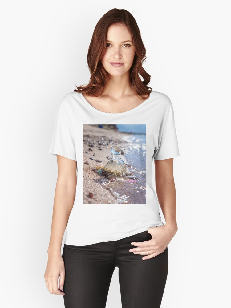 A bottle with seashells embedded in the sand on the beach  Women's Relaxed Fit T-Shirt Front
