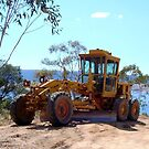 Grader by Caterpillar by buildings