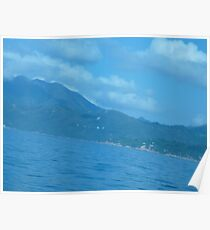 Puffy clouds floating over Island Poster