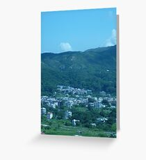 Mountains surrounding a little village Greeting Card