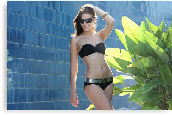 Portrait of a seductive female model in bikini posing in front of blue wall by Anton Oparin