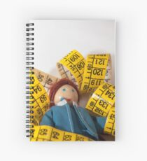 Doll resting on measuring tape Spiral Notebook