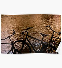 Silhouetted bicycles along a canal in Amsterdam, Holland Poster