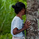 Balinese woman with a tree in Eastern Bali, Indonesia by Michael Brewer