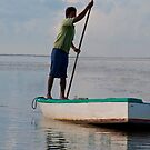 Fisherman poling his boat off Sanur Beach in Bali, Indonesia by Michael Brewer