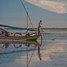 Fisherman on an outrigger canoe at Sanur Beach, in Bali, Indonesia by Michael Brewer