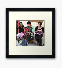 A musician entertaining his family. Framed Print