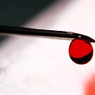 Drop of blood at the end of a syringe. by Sami Sarkis