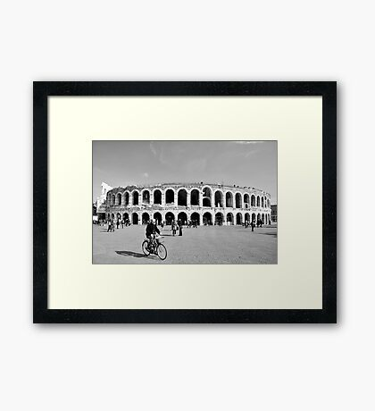 Cycling by the Arena Framed Print