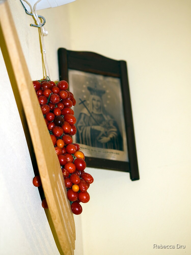 A bunch of tomatoes on a hook by Rebecca Dru