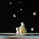 Drop of milk splashing in a glass. by Sami Sarkis