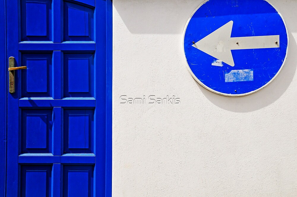 Street arrow sign and blue door on white wall by Sami Sarkis