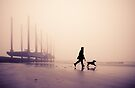 Man and Labrador on the beach at Newhaven, East Sussex by Heather Buckley