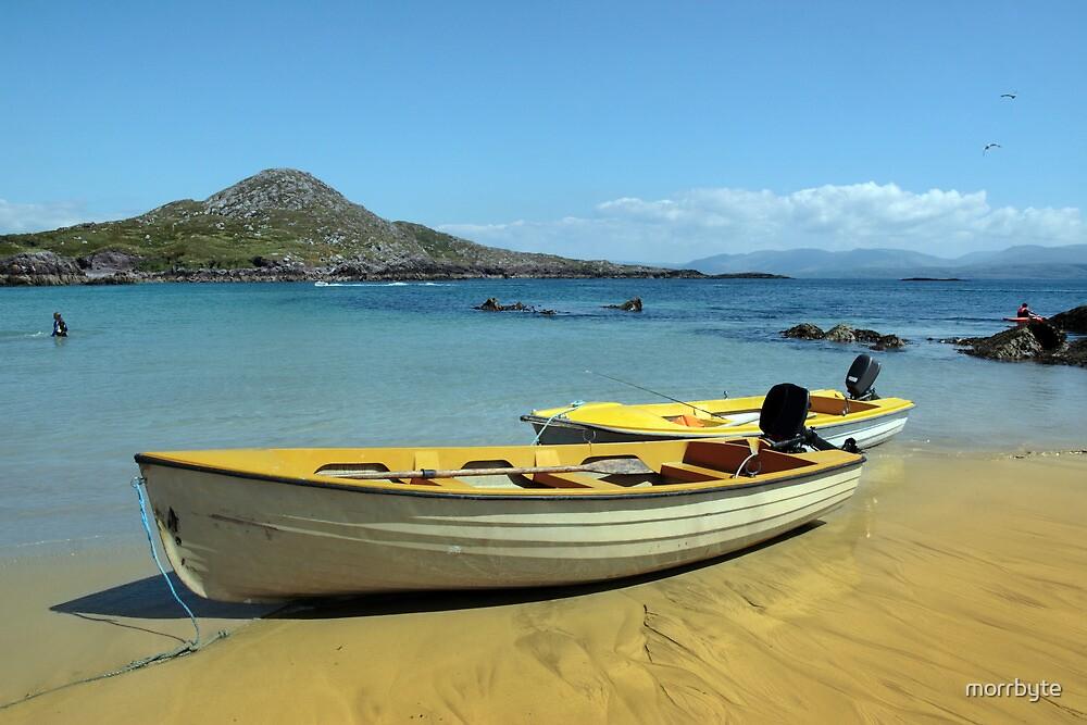 yellow boats on golden irish beach by morrbyte