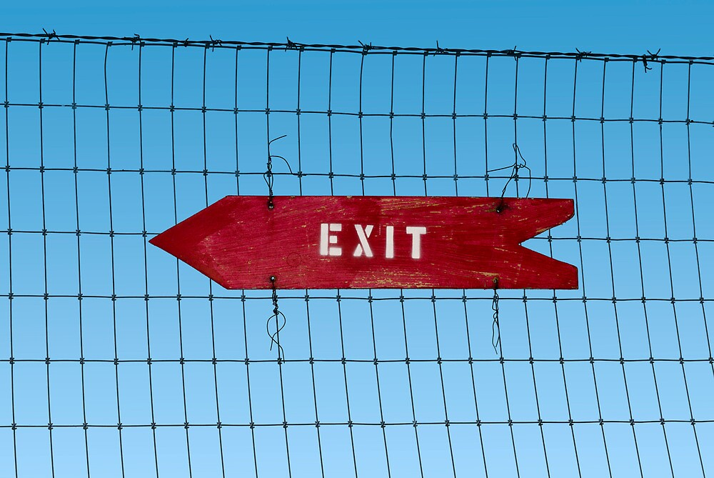 Wooden arrow sign on fence with word 'Exit' by Jeff Knapp
