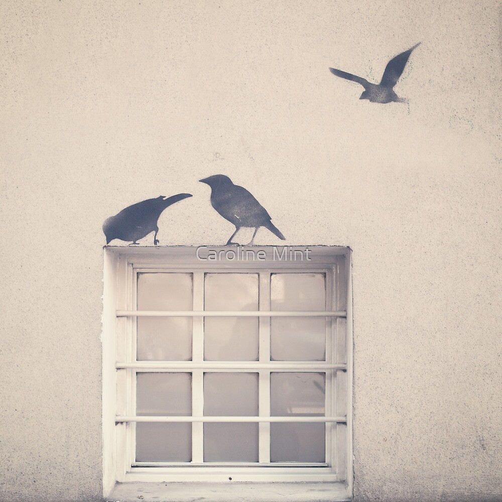 Painted bird over a window in a beige wall by Caroline Mint