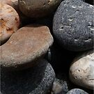 tumbling pebbles on a beach by battered-books