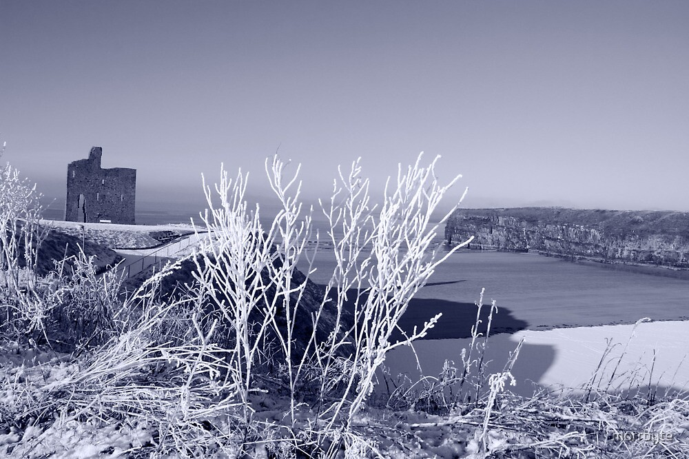 christmas day view of ballybunion castle and beach in snow by morrbyte