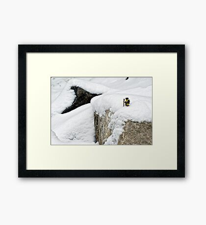 Hiker on snowy cliff Framed Print