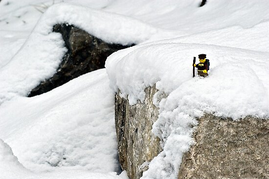 Hiker on snowy cliff by Dan Phelps