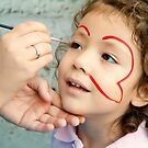 Little Girl Getting Her Face Painted by Kuzeytac