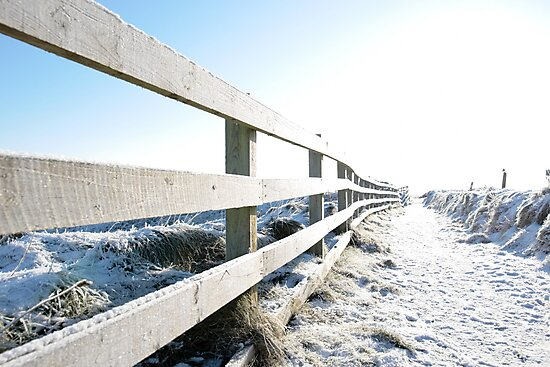 snow covered path on cliff edge fenced walk by morrbyte