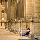 A couple search their guide book at the Louvre, Paris by Elana Bailey
