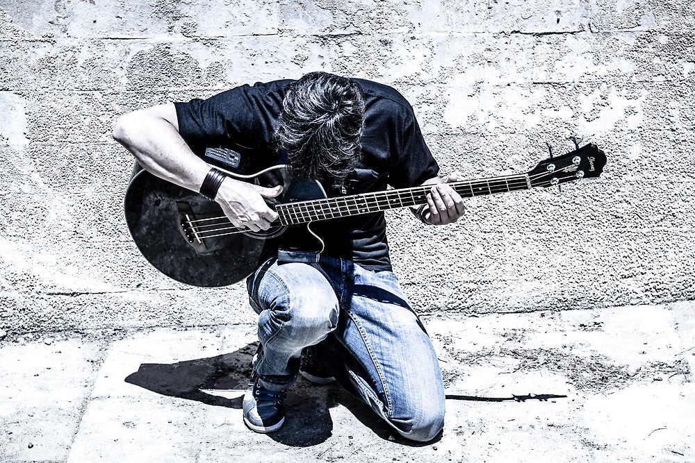 man playing acoustic guitar kneeling  by Peter Noyce