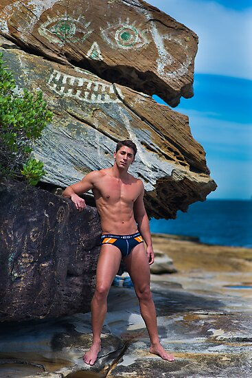 Man in speedos at beach with modern rock art by RodSydney