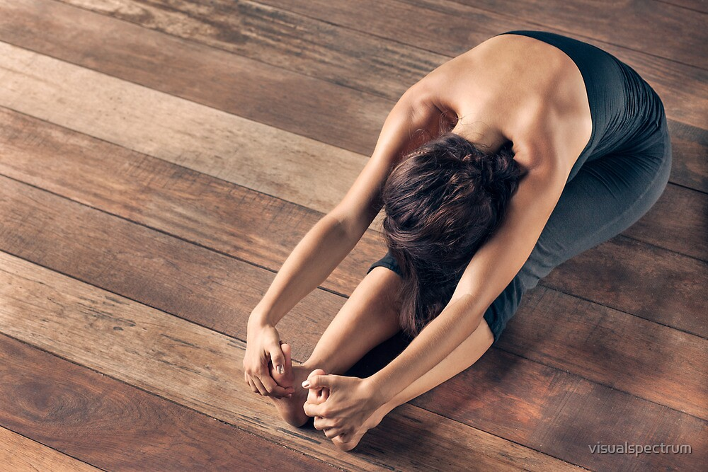 Yoga: Young Woman Doing Forward Bend by visualspectrum