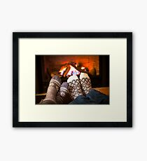 Feet warming by fireplace Framed Print