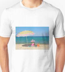 little girl sitting on beach under sunshade Unisex T-Shirt