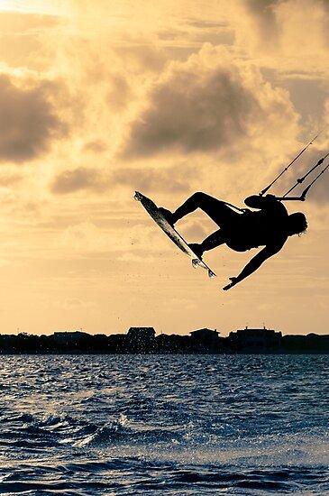 Silhouette of a kitesurfer flying by homydesign