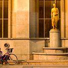 A cyclist near the Eiffel Tower in Paris, phones a friend by Elana Bailey