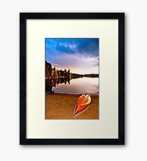 Lake sunset with canoe on beach Framed Print