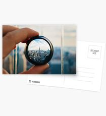 Man holding a lens over Manhattan Postcards