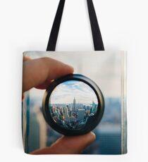 Man holding a lens over Manhattan Tote Bag