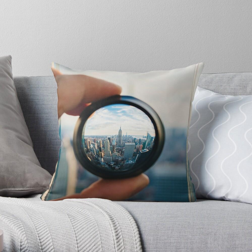Hombre sosteniendo una lente sobre Manhattan Cojín