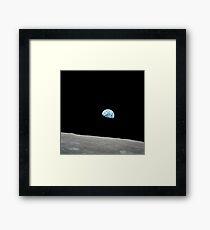 Earth rising above the lunar horizon. Framed Print
