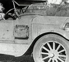 Black and white photo of Dachshund in old car. Sticker