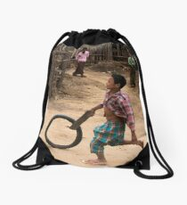 A Child Playing With A Wheel in Myanmar Drawstring Bag