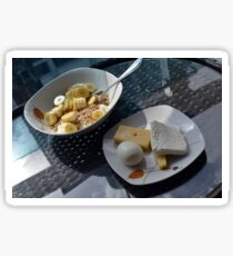 A bowl of cereals and yogurt and a plate with cheese and eggs. Sticker