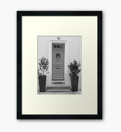 Door framed with green plants Framed Print