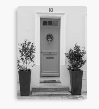 Door framed with green plants Canvas Print