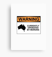WARNING: CURRENTLY OPERATED BY MORONS Canvas Print