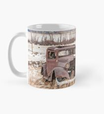 Rusty Antique Vehicle in a Field Covered with Snow Mug