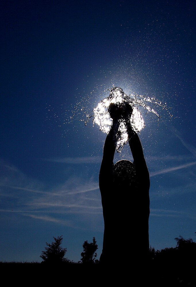 Man bursting a water balloon in silhouette by turniptowers