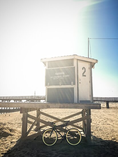 Bike leaning against lifeguard hut on beach by Bradley Hebdon